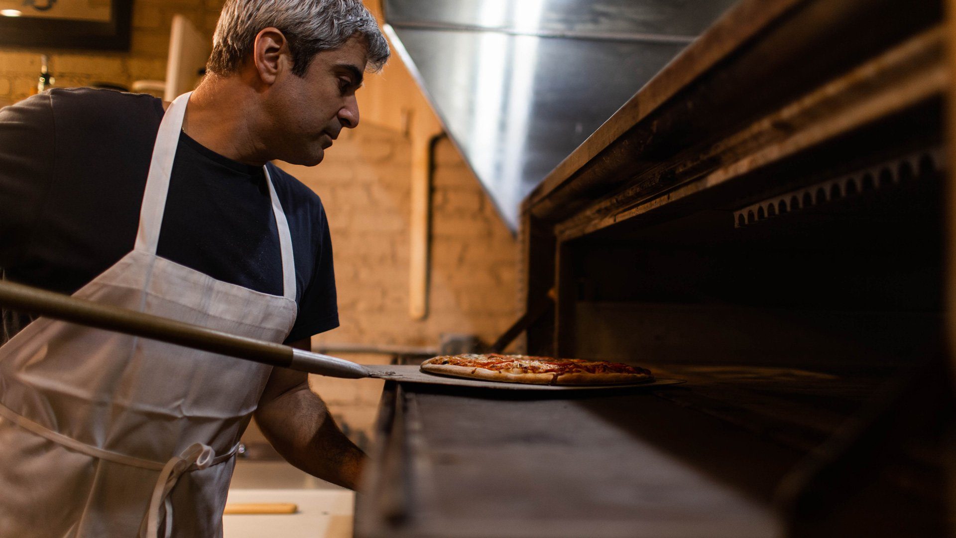 Pizzaiolo inforna una pizza